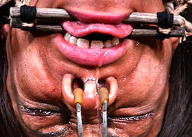 Cruel facial torture of suspended upside down slave