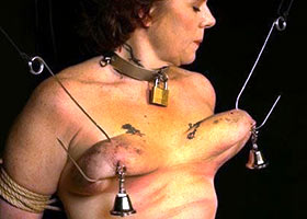 Woman suspended by huge hooks in her tits