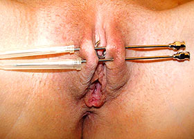 Sister shows insertion of long needles in her labia
