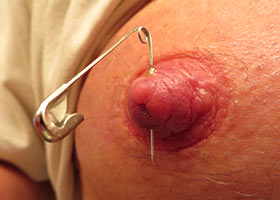 Piercing of own nipples by safety pins